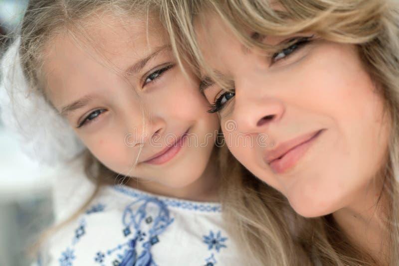 Πορτρέτο κινηματογραφήσεων σε πρώτο πλάνο της ευτυχούς εύθυμης όμορφης νέας μητέρας με την λίγη χαμογελώντας κόρη στοκ φωτογραφίες