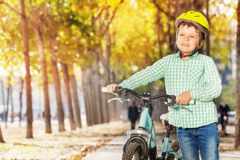 Πορτρέτο κινηματογραφήσεων σε πρώτο πλάνο του αγοριού με το ποδήλατο στο πάρκο φθινοπώρου στοκ εικόνα με δικαίωμα ελεύθερης χρήσης