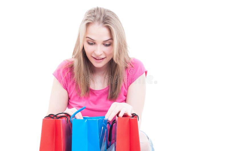 Πορτρέτο κινηματογραφήσεων σε πρώτο πλάνο του εύθυμου κοριτσιού που εξετάζει μια τσάντα δώρων στοκ εικόνες