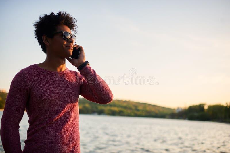 Πορτρέτο κινηματογραφήσεων σε πρώτο πλάνο του εύθυμου νεαρού άνδρα που κάνει ένα τηλεφώνημα στοκ εικόνες