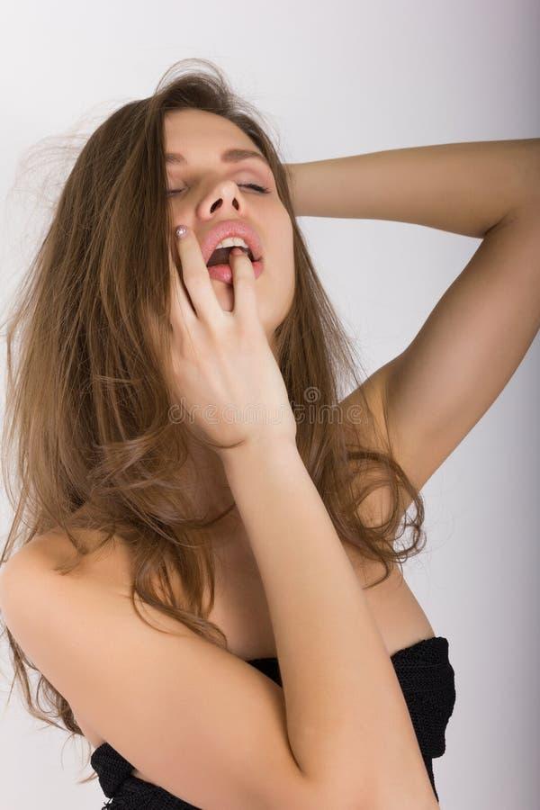 Πορτρέτο κινηματογραφήσεων σε πρώτο πλάνο του προκλητικού ξανθού κοριτσιού που δαγκώνει ήπια το δάχτυλό της στοκ εικόνες