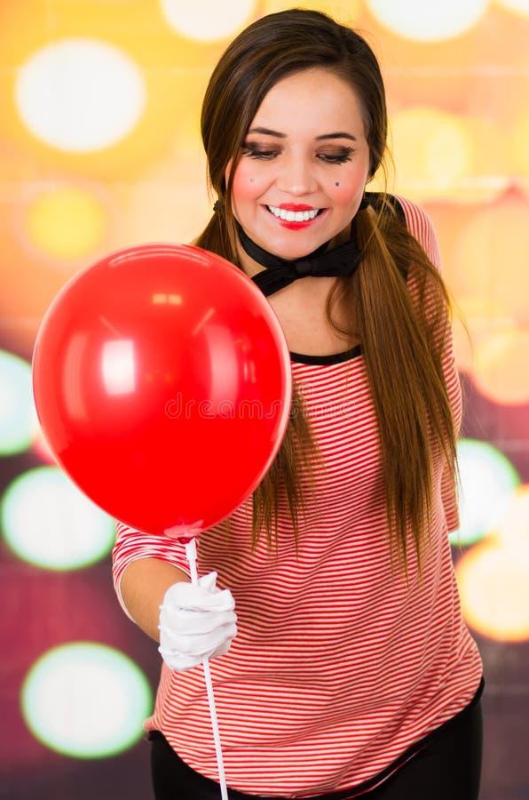 Πορτρέτο κινηματογραφήσεων σε πρώτο πλάνο του χαριτωμένου κόκκινου μπαλονιού εκμετάλλευσης κλόουν νέων κοριτσιών mime στοκ εικόνα με δικαίωμα ελεύθερης χρήσης