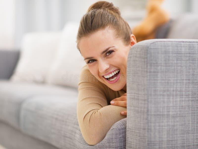 Πορτρέτο κοιτάγματος γυναικών χαμόγελου του νέου έξω από το ντιβάνι στοκ φωτογραφίες