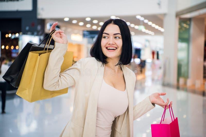 Πορτρέτο κοριτσιών αγορών μόδας Γυναίκα ομορφιάς με τις τσάντες αγορών στη λεωφόρο αγορών Αγοραστής πωλήσεις αγορές κεντρικών εσω στοκ φωτογραφίες