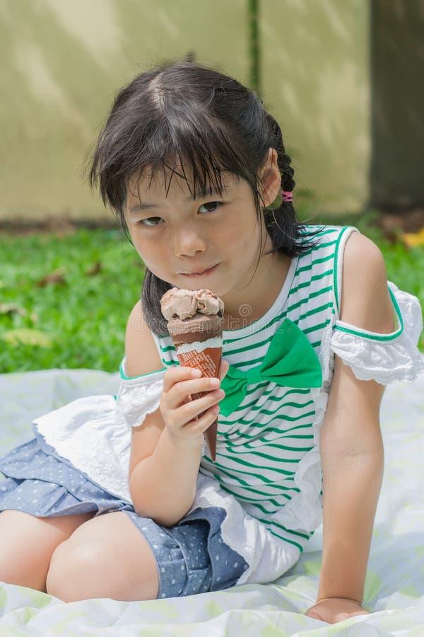 Πορτρέτο κοριτσιών και παιδιών βλαστών στον κήπο και έχει την κατανάλωση του παγωτού στοκ εικόνες