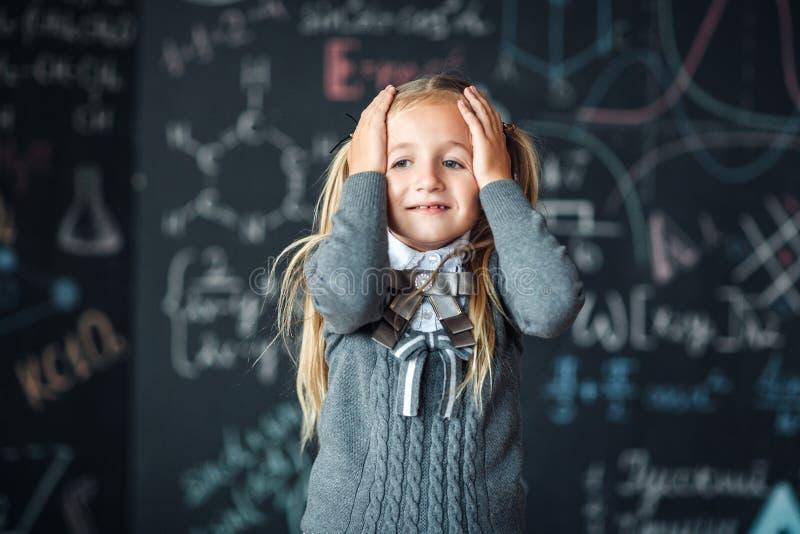 Πορτρέτο λίγου ξανθού κοριτσιού, που αρπάζει το κεφάλι της πίνακας κιμωλίας με τους σχολικούς τύπους στο υπόβαθρο, φωτογραφία ένν στοκ εικόνες με δικαίωμα ελεύθερης χρήσης