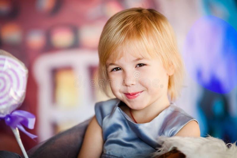 Πορτρέτο λίγου ξανθού χαμογελώντας κοριτσιού που παίζει με την καραμέλα παιχνιδιών Χριστούγεννα και νέο θέμα έτους στοκ εικόνες με δικαίωμα ελεύθερης χρήσης