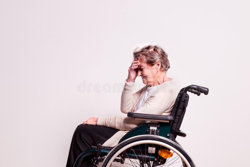 Πορτρέτο μιας ανώτερης γυναίκας με την αναπηρική καρέκλα στο στούντιο στοκ εικόνες