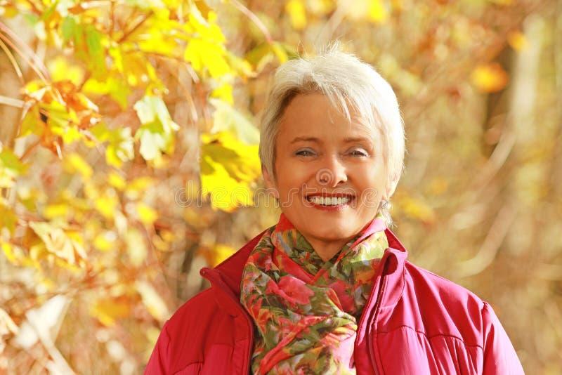 Πορτρέτο μιας ανώτερης ευτυχούς γυναίκας μπροστά από τα φύλλα φθινοπώρου στοκ φωτογραφία με δικαίωμα ελεύθερης χρήσης