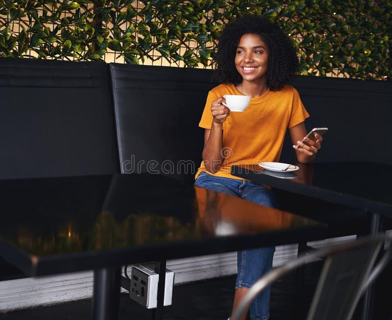 Πορτρέτο μιας αφρικανικής νέας συνεδρίασης γυναικών στον καφέ στοκ εικόνες