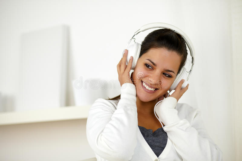 Γοητευτική γυναίκα με τη μουσική ακούσματος ακουστικών στοκ φωτογραφία με δικαίωμα ελεύθερης χρήσης