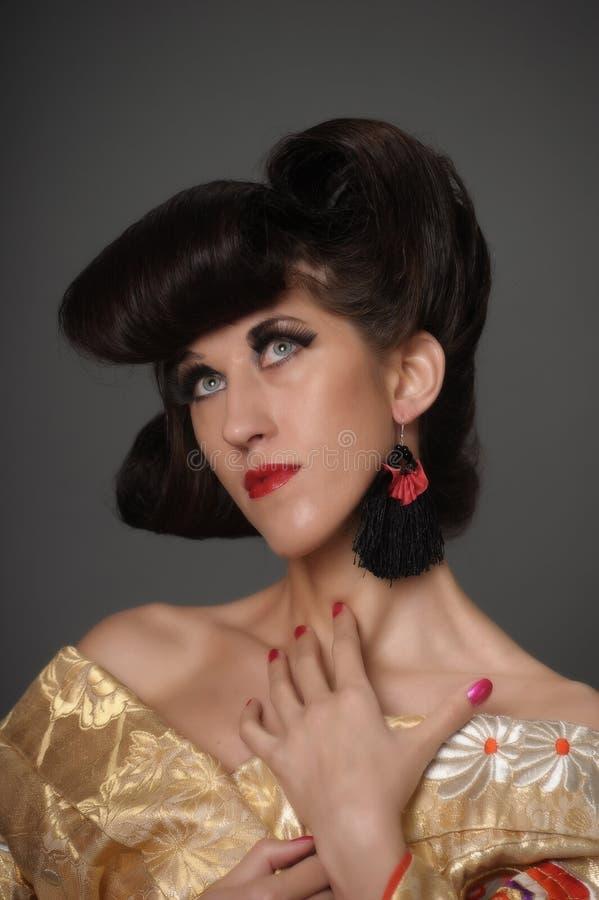 Πορτρέτο μιας γυναίκας με ένα δημιουργικό ασιατικό hairdo και ένα μακροχρόνιο ey στοκ εικόνες