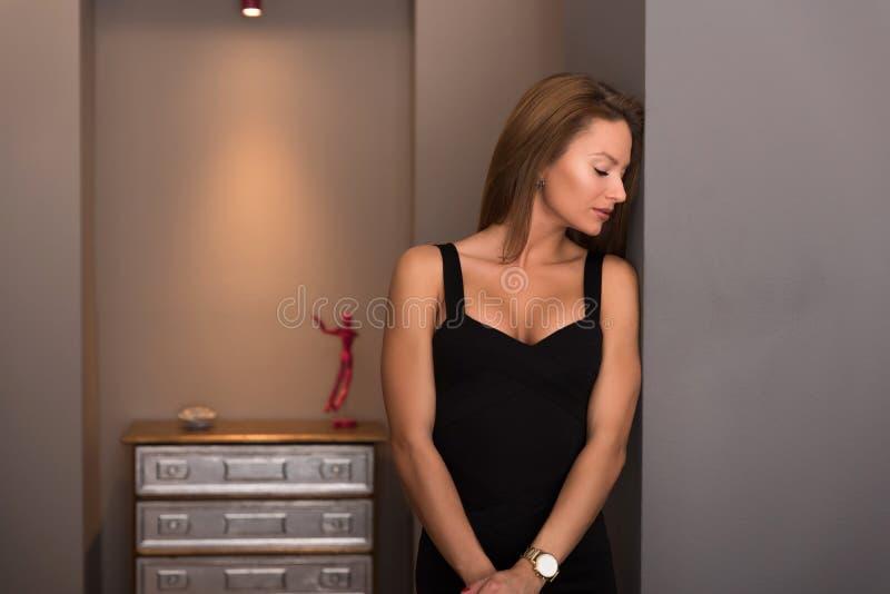 Πορτρέτο μιας γυναίκας με κομψό φόρεμα που στέκεται σε μια κρεβατοκάμαρα στοκ εικόνες με δικαίωμα ελεύθερης χρήσης