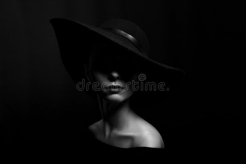 Πορτρέτο μιας γυναίκας σε ένα μαύρο καπέλο σε μια μαύρη γραπτή φωτογραφία υποβάθρου στοκ φωτογραφίες