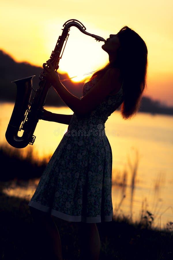 Πορτρέτο μιας γυναίκας σε ένα φόρεμα που παίζει το saxophone κοντά στον ποταμό στοκ φωτογραφίες