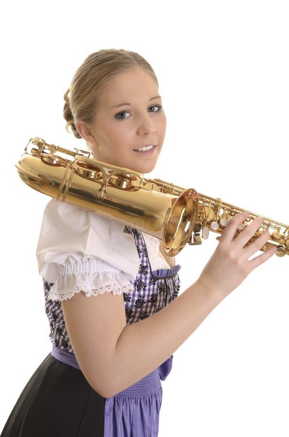 Πορτρέτο μιας γυναίκας στο φόρεμα dirndl με το saxophone στοκ εικόνα με δικαίωμα ελεύθερης χρήσης