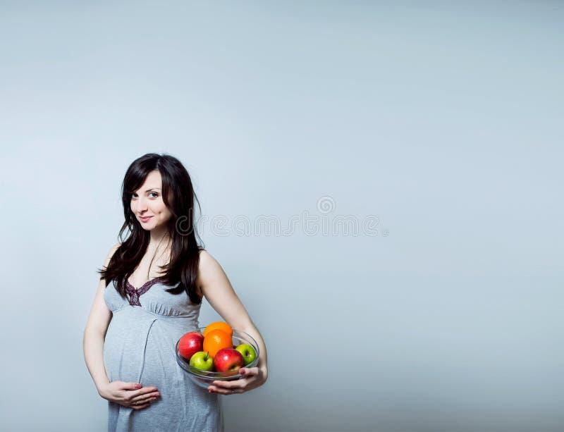 Πορτρέτο μιας εγκύου γυναίκας με τα ζωηρόχρωμα φρούτα στοκ φωτογραφία με δικαίωμα ελεύθερης χρήσης