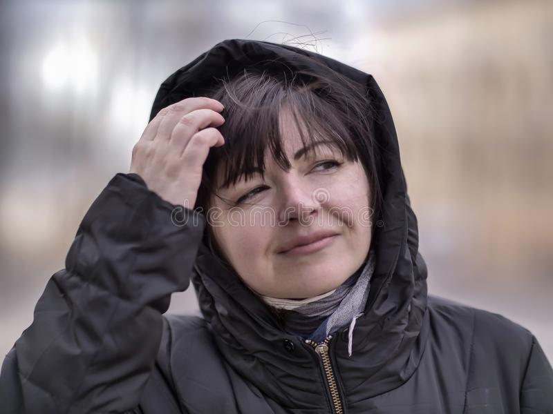 Πορτρέτο μιας ελκυστικής νέας γυναίκας σε ένα μαύρο σακάκι με μια κουκούλα στα πλαίσια της οδού, κινηματογράφηση σε πρώτο πλάνο στοκ εικόνα