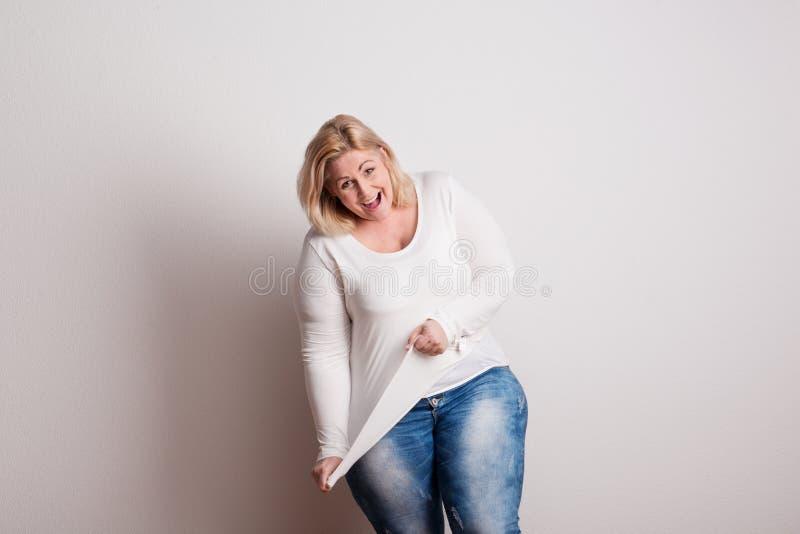 Πορτρέτο μιας ελκυστικής υπέρβαρης γυναίκας στο στούντιο σε ένα άσπρο υπόβαθρο στοκ φωτογραφία με δικαίωμα ελεύθερης χρήσης