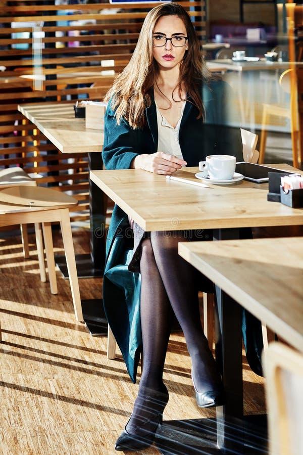 Πορτρέτο μιας επιχειρησιακής γυναίκας με τα εργαλεία γραφείων που κάθεται με ενώ έχοντας ένα φλιτζάνι του καφέ στοκ φωτογραφία