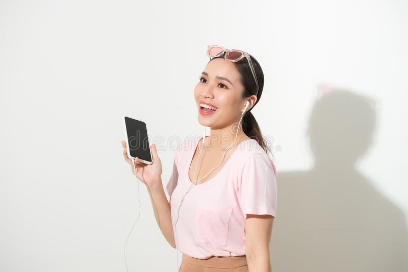 Πορτρέτο μιας ευτυχούς μουσικής ακούσματος γυναικών στα ακουστικά και χορός που απομονώνεται σε ένα άσπρο υπόβαθρο στοκ φωτογραφία με δικαίωμα ελεύθερης χρήσης