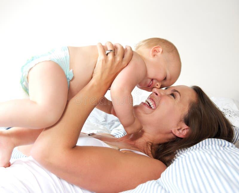 Πορτρέτο μιας εύθυμης μητέρας και ενός χαριτωμένου παιχνιδιού μωρών στοκ εικόνα