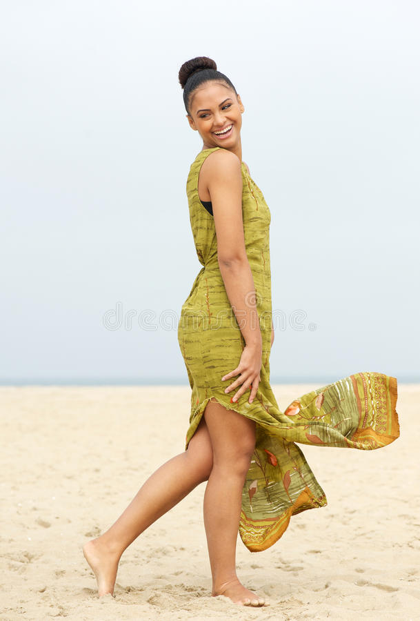 Πορτρέτο μιας εύθυμης νέας γυναίκας που περπατά στην παραλία στοκ φωτογραφίες