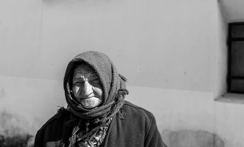 Πορτρέτο μιας ηλικιωμένης γυναίκας επαιτών στις μεσαιωνικές οδούς σε γραπτό στοκ φωτογραφία με δικαίωμα ελεύθερης χρήσης