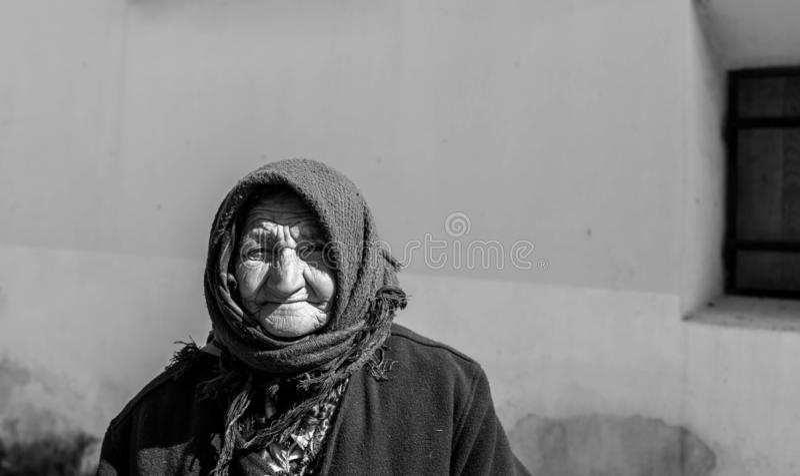 Πορτρέτο μιας ηλικιωμένης γυναίκας επαιτών στις μεσαιωνικές οδούς σε γραπτό στοκ εικόνες με δικαίωμα ελεύθερης χρήσης