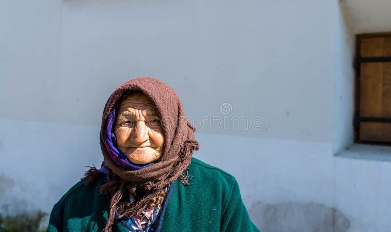 Πορτρέτο μιας ηλικιωμένης γυναίκας επαιτών στις μεσαιωνικές οδούς στοκ εικόνες