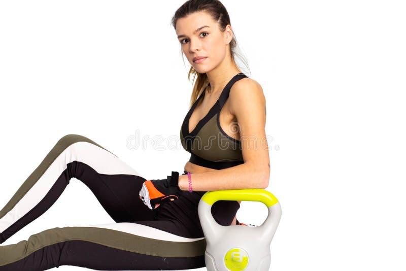 Πορτρέτο μιας κατάλληλης νέας γυναίκας που παίρνει ένα σπάσιμο ένα άσπρο κίτρινο με ένα kettlebell εικόνα στοκ εικόνες