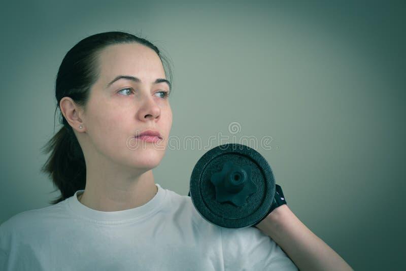 Πορτρέτο μιας λευκιάς καυκάσιας γυναίκας που κρατά τη βαριά κινηματογράφηση σε πρώτο πλάνο αλτήρων σιδήρου στοκ εικόνες