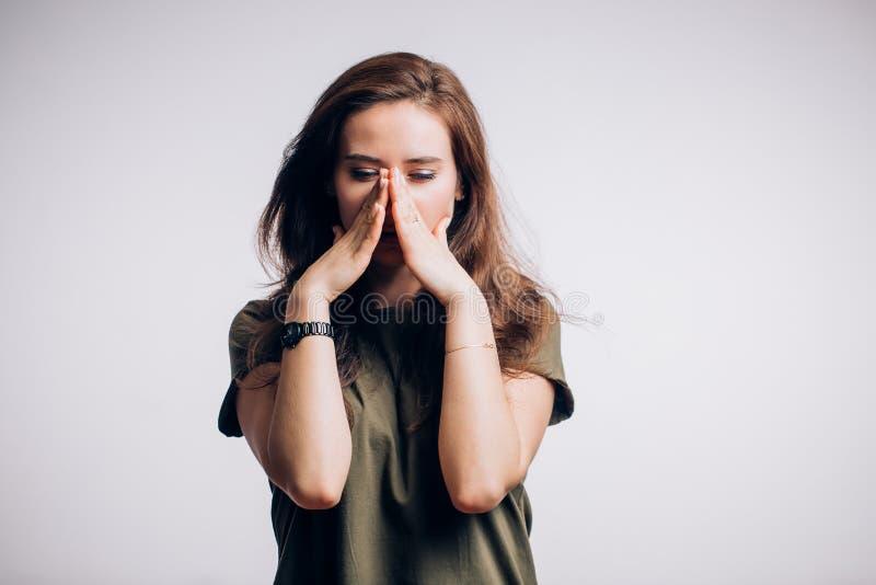 Πορτρέτο μιας λυπημένης γυναίκας σε ένα άσπρο υπόβαθρο Στενοχωρημένη γυναίκα που κοιτάζει κάτω στοκ φωτογραφία με δικαίωμα ελεύθερης χρήσης