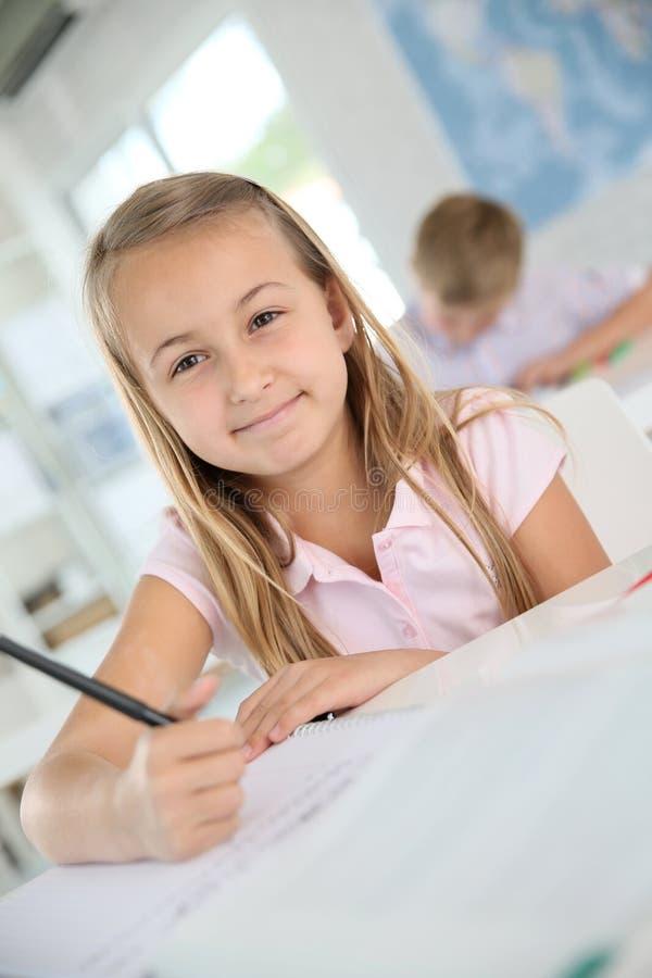 Πορτρέτο μιας μαθήτριας που γράφει κάτω στο σημειωματάριο στοκ εικόνες
