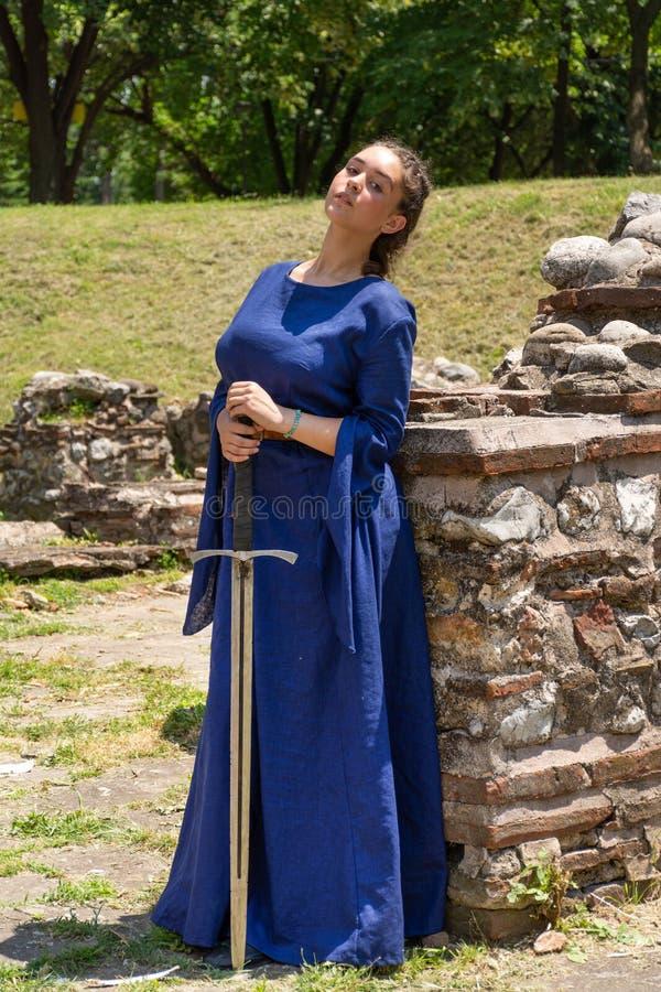 Πορτρέτο μιας μεσαιωνικής κυρίας σε ένα μπλε φόρεμα που κρατά ένα ξίφος στα χέρια της στοκ εικόνα με δικαίωμα ελεύθερης χρήσης