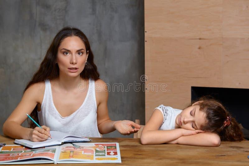 Πορτρέτο μιας μητέρας που βοηθά τη μικρή γλυκιά και χαριτωμένη κόρη της για να κάνει την εργασία της στο εσωτερικό r στοκ φωτογραφίες με δικαίωμα ελεύθερης χρήσης