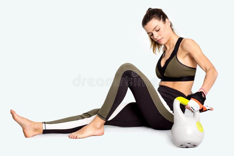 Πορτρέτο μιας νέας γυναίκας κατά τη διάρκεια ενός σπασίματος μετά από το workout με το kettlebell εικόνα στοκ φωτογραφία με δικαίωμα ελεύθερης χρήσης