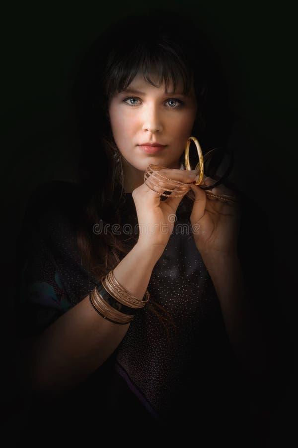 Πορτρέτο μιας νέας γυναίκας με τα χρυσά βραχιόλια στοκ εικόνες με δικαίωμα ελεύθερης χρήσης