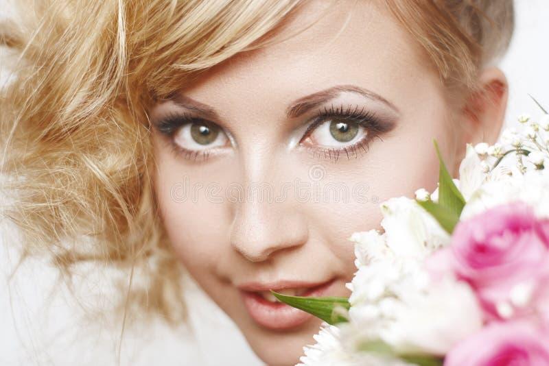 Πορτρέτο μιας νέας γυναίκας με την ξανθά σγουρά τρίχα και τα λουλούδια στοκ φωτογραφία