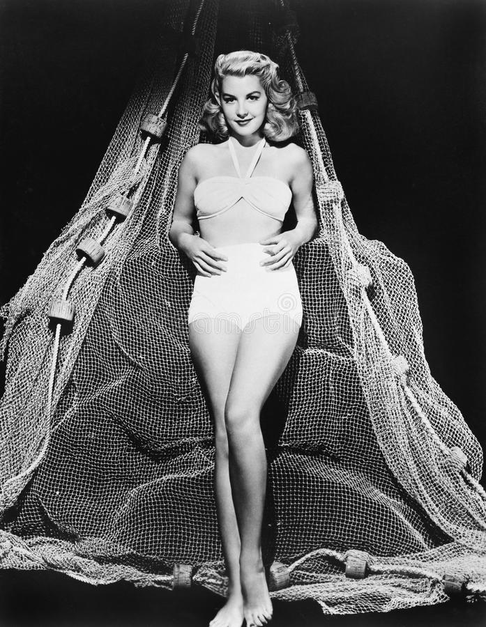Πορτρέτο μιας νέας γυναίκας μπροστά από ένα δίχτυ του ψαρέματος (όλα τα πρόσωπα που απεικονίζονται δεν ζουν περισσότερο και κανέν στοκ εικόνες