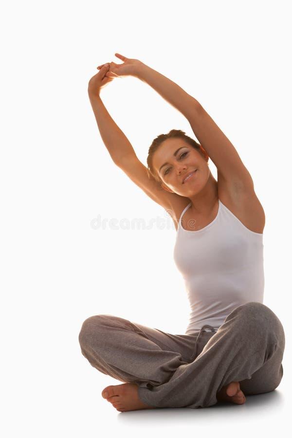 Πορτρέτο μιας νέας γυναίκας που τεντώνει την πίσω στοκ εικόνα