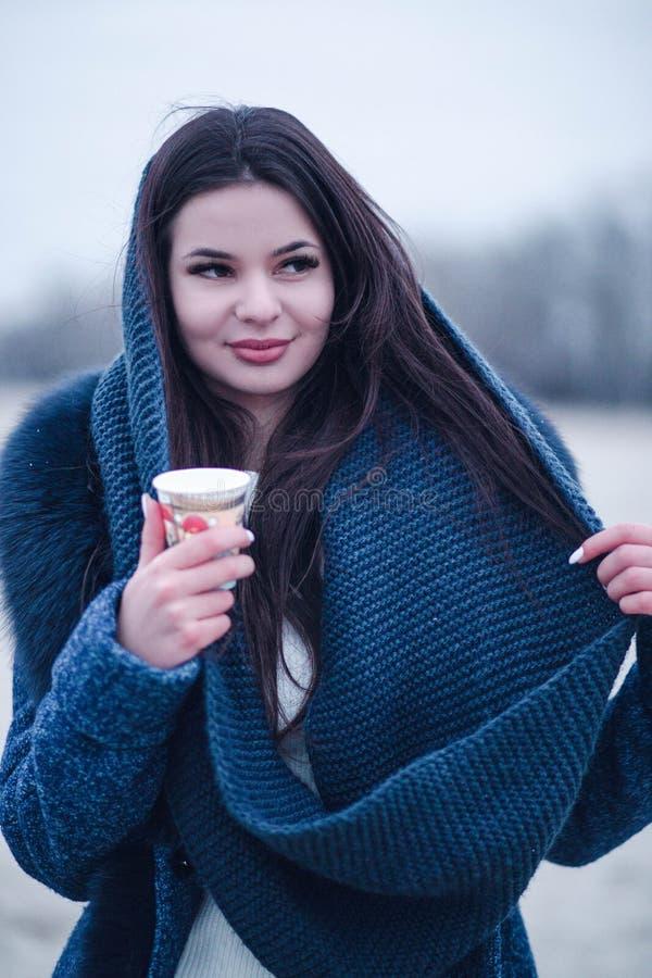 Πορτρέτο μιας νέας γυναίκας σε ένα παλτό με ένα περιλαίμιο που πίνει τον καφέ στην οδό στοκ εικόνες