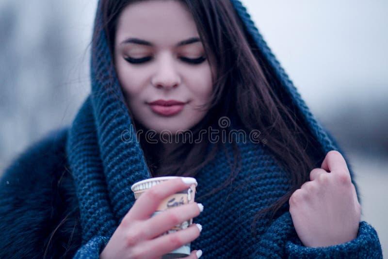 Πορτρέτο μιας νέας γυναίκας σε ένα παλτό με ένα περιλαίμιο που πίνει τον καφέ στην οδό στοκ φωτογραφίες