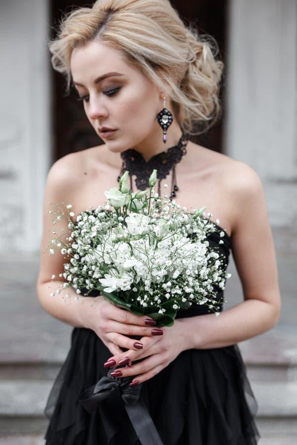 Πορτρέτο μιας νέας γυναίκας στο μαύρο φόρεμα με τα λουλούδια γάμος στοκ φωτογραφία με δικαίωμα ελεύθερης χρήσης