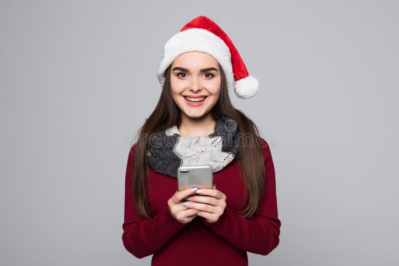 Πορτρέτο μιας νέας γυναίκας brunette σε κόκκινο Άγιο Βασίλη που χρησιμοποιεί το κινητό τηλέφωνο που απομονώνεται στο γκρίζο υπόβα στοκ φωτογραφίες