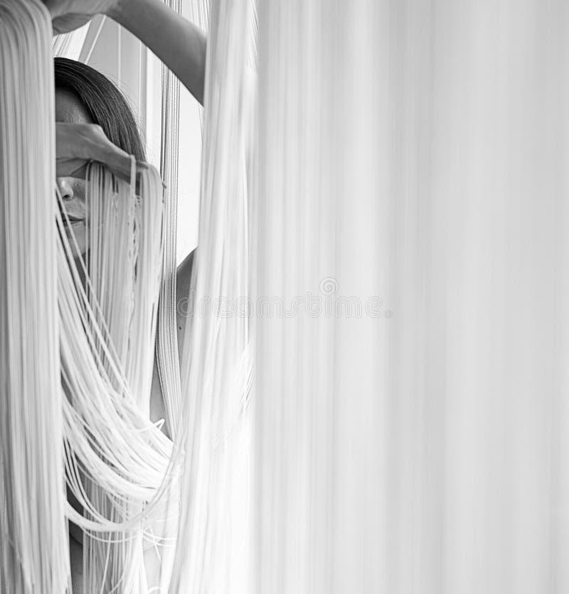 Πορτρέτο μιας νέας ελκυστικής γυναίκας με τους αποκαλυμμένους ώμους που τραβούν decoratively τα νήματα μιας κουρτίνας σειράς με τ στοκ φωτογραφία με δικαίωμα ελεύθερης χρήσης