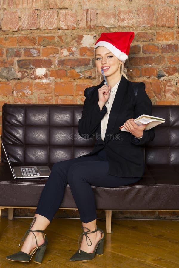 Πορτρέτο μιας νέας επιχειρησιακής γυναίκας ομορφιάς που χρησιμοποιεί το lap-top στο γραφείο πριν από το νέο έτος με το καπέλο san στοκ φωτογραφία