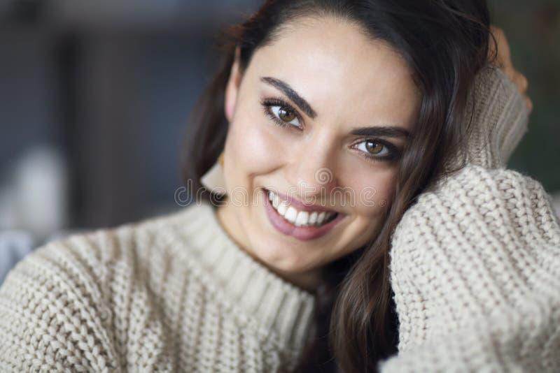Πορτρέτο μιας νέας ευτυχούς όμορφης γυναίκας στο θερμό ιματισμό στο σπίτι στοκ εικόνες