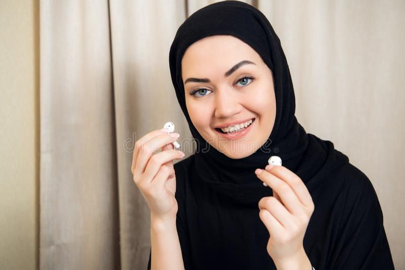 Πορτρέτο μιας νέας και ελκυστικής μουσουλμανικής γυναίκας σε ένα τουρμπάνι ή hijab του ακούσματος τη μουσική ροής στο smartphone  στοκ φωτογραφία
