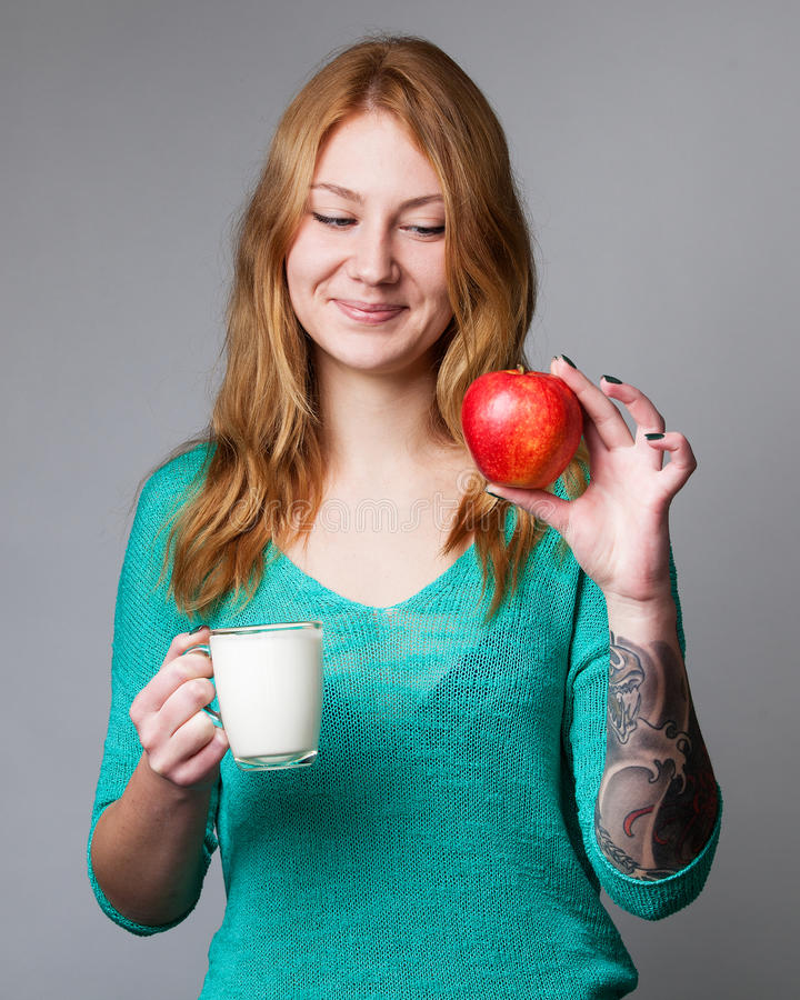 Πορτρέτο μιας νέας κυρίας πιπεροριζών στην τυρκουάζ μπλούζα με ένα φλυτζάνι ο στοκ εικόνα με δικαίωμα ελεύθερης χρήσης